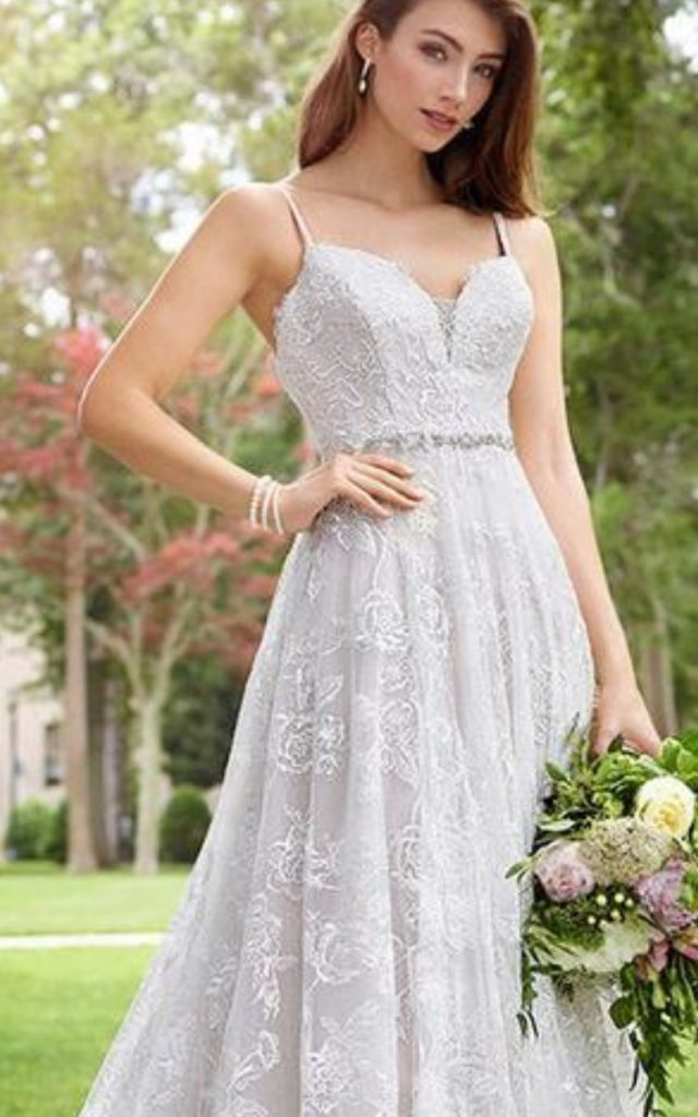 Superb Toccata is an embroidered lace, tulle, and sequin over chiffon and satin sleeveless A-line gown featuring lace accented thin straps, a curved deep V-neckline with an illusion modesty panel, a beaded natural waist, a slightly curved back, a scalloped hem and a chapel train. Bridal shop in Colorado Springs, CO- Bridal Elegance