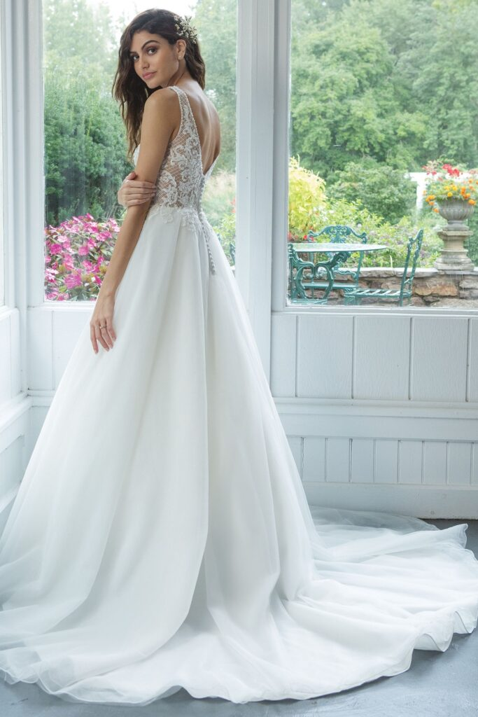 Feel romantic and beautiful in this ball gown. The illusion V-neckline on front and back is accented with lattice beaded lace. Complete the look with a tulle circular cut skirt with a chapel length train. Bridal store in Colorado Springs, CO Bridal Elegance