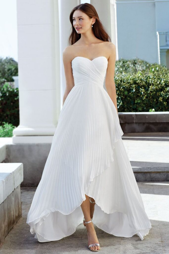 An asymmetrical high-low wedding gown. A ruched bodice defines the modified sweetheart neckline and empire waist. The look is tied together with an accordion pleated chiffon skirt. Bridal store in Colorado Springs, CO - Bridal Elegance