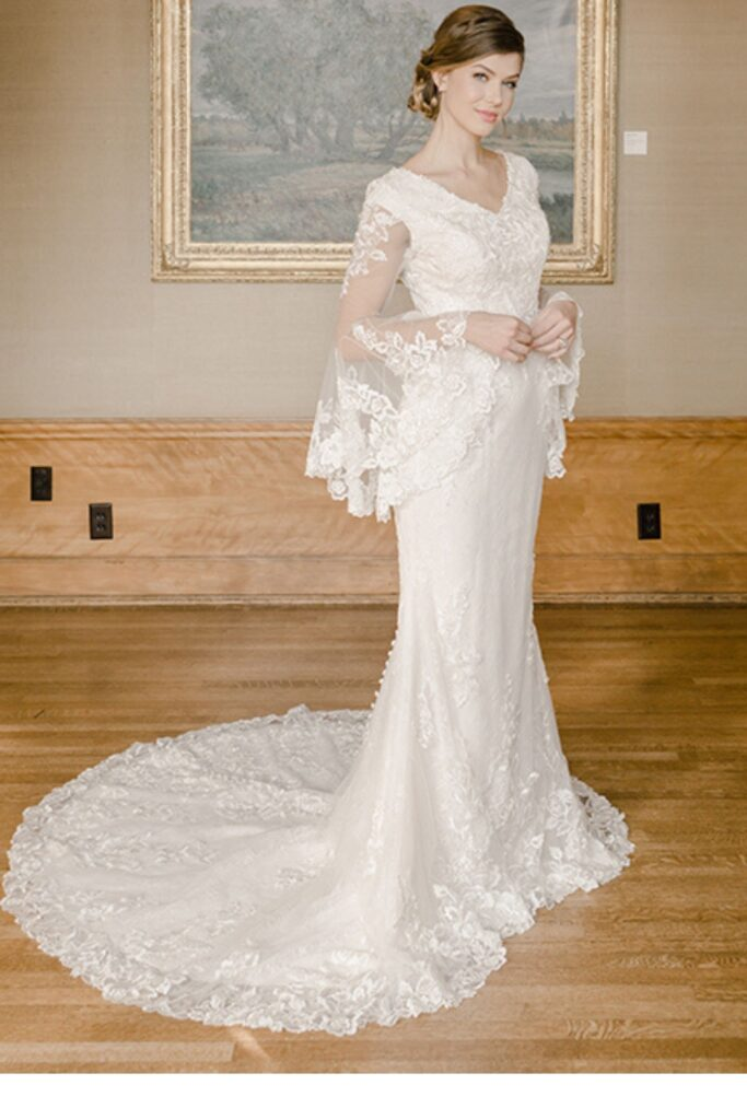 Lace and chiffon fit and flare bridal gown features lace appliques over allover lace. With a V-neckline, illusion lace bell sleeves. Bridal store in Colorado Springs, Colorado Bridal Elegance